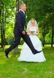 lycklig banhoppning för brudgum mycket Arkivbilder