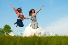 Lycklig banhoppning för härliga unga kvinnor på den blåa skyen Royaltyfria Foton