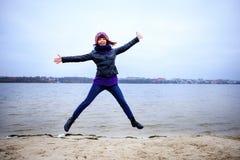 Lycklig banhoppning för ung kvinna på stranden i höst arkivbild