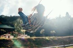 Lycklig barfota flicka på gunga i solljus arkivfoto