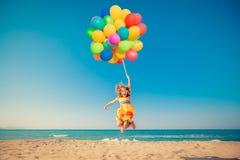 Lycklig barnbanhoppning med färgrika ballonger på den sandiga stranden arkivfoton