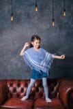 Lycklig barndans på den moderna soffan Royaltyfria Foton