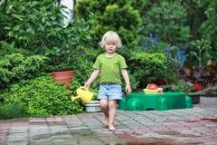 Lycklig barndom - den barfota flickan med att bevattna kan arkivfoto