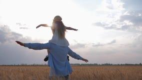 Lycklig barndom, den unga pappan med den ganska haired dottern på hans skuldror kör fördelning av hans armar till sidan som nivån lager videofilmer