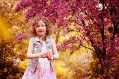 Lycklig barnflicka, i att spela för rosa färgklänning som är utomhus- i vårträdgård nära blommande crabappleträd Arkivfoto