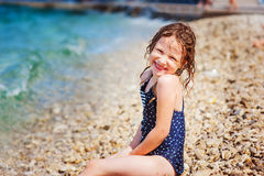 Lycklig barnflicka i baddräkt som kopplar av på stranden och spelar med vatten Sommarsemester på havet Arkivbild