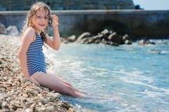 Lycklig barnflicka i baddräkt som kopplar av på stranden och spelar med vatten Sommarsemester på havet Arkivbilder