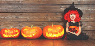 Lycklig barnflicka i dräkthäxan för allhelgonaafton med pumpor Arkivbild