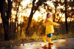 Lycklig barnflicka i gula laganmdgummistöveler som hoppar i pöl royaltyfria foton