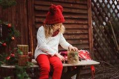 Lycklig barnflicka i röd hatt och halsduken som slår in julgåvor på det hemtrevliga landshuset som dekoreras för nytt år och jul Royaltyfri Bild