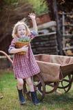 Lycklig barnflicka med blåklockor i vårträdgård nära skottkärran arkivbild