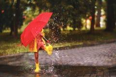 Lycklig barnflicka med ett paraply och gummistöveler i pöl på arkivbild