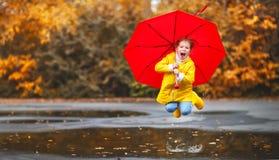 Lycklig barnflicka med ett paraply och gummistöveler i pöl på Royaltyfri Bild