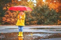 Lycklig barnflicka med ett paraply och gummistöveler i pöl på Arkivbilder