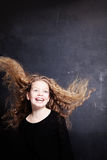 Lycklig barnflicka med långt lockigt hår arkivbild