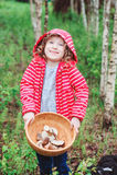 Lycklig barnflicka med lösa ätliga lösa champinjoner på träplattan Fotografering för Bildbyråer