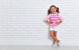 Lycklig barnflicka nära en tom tegelstenvägg Arkivfoton