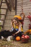Lycklig barnflicka och hennes hund som väljer nya äpplen på lantgården Landsbygdsboendebegrepp arkivbild