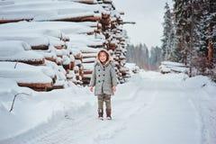 Lycklig barnflicka på vägen i snöig skog för vinter med trädet som avverkar på bakgrund Royaltyfri Fotografi