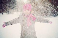 Lycklig barnflicka som har gyckel som spelar med snö Royaltyfria Bilder