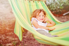 Lycklig barnflicka som kopplar av i hängmatta i sommar Fotografering för Bildbyråer