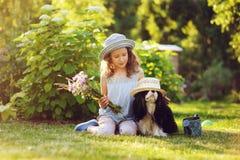 Lycklig barnflicka som kopplar av i sommarträdgård med hennes spanielhund arkivbilder