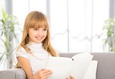 Lycklig barnflicka som läser en bok, medan sitta på soffan Arkivfoton