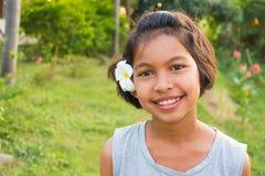 Lycklig barnflicka som ler med blomman på hennes framsida på soligt fält Arkivbild