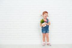 Lycklig barnflicka som skrattar och rymmer krukan med den inlagda växten nära Royaltyfri Bild