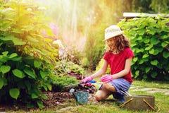 lycklig barnflicka som spelar den lilla trädgårdsmästaren och hjälper i sommarträdgård, bärande hatt och handskar Arkivfoton