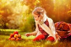 Lycklig barnflicka som spelar med äpplen i höstträdgård Arkivbilder