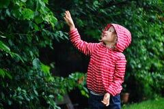 Lycklig barnflicka som spelar under regnet i sommarträdgård Royaltyfria Bilder
