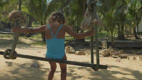 Lycklig barnflicka som svänger på den tropiska sandiga stranden arkivfilmer