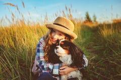 Lycklig barnflicka som tycker om sommarsemestrar med hennes hund, går och spelar på solig äng royaltyfri foto