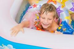 Lycklig barnflickasimning i pöl med simningcirkeln Arkivfoton
