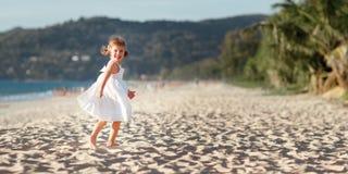 Lycklig barnflickaspring på stranden vid havet i sommar royaltyfri fotografi