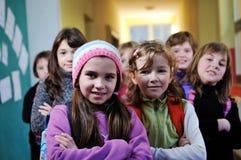 Lycklig barngrupp i skola Arkivbilder