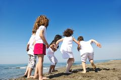 Lycklig barngrupp som leker på strand Royaltyfri Bild