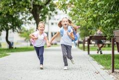 Lycklig barnkörning från skola med ryggsäckar Begreppet av skolan, studie, utbildning, kamratskap, barndom royaltyfria foton
