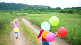 Lycklig barnkörning på en skogväg med ballonger Födelsedagberöm i parkera Skratt och glädje av barn stock video