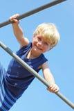 Lycklig barnklättring på lekplatsen Fotografering för Bildbyråer