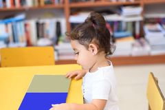Lycklig barnliten flicka som l?ser en bok royaltyfri fotografi