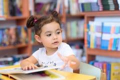Lycklig barnliten flicka som l?ser en bok arkivfoton