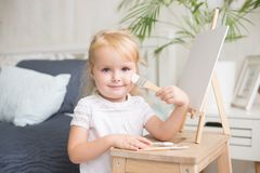 Lycklig barnmålning med gouache och vattenfärgen målar på staffli inomhus arkivbild