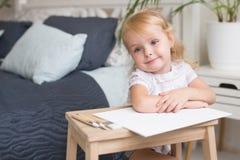 Lycklig barnmålning med gouache och vattenfärgen målar på staffli inomhus royaltyfri foto