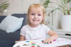 Lycklig barnmålning med gouache och vattenfärgen målar på staffli inomhus royaltyfria bilder