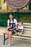 Lycklig barnmoder med en gullig dotter på en bänk med en klubba i händer i identiska klänningar Royaltyfri Foto