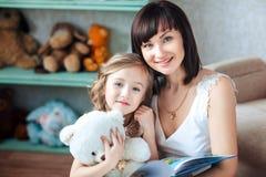 Lycklig barnmoder med hennes dottersammanträde i ett rum med en bok i henne händer Closeup av le royaltyfria foton