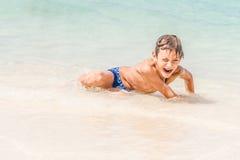 Lycklig barnpojke som har gyckel i vatten, tropisk sommarvacat Royaltyfri Foto