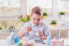 Lycklig barnpojke som har gyckel under målningägg för easter i sp arkivfoton